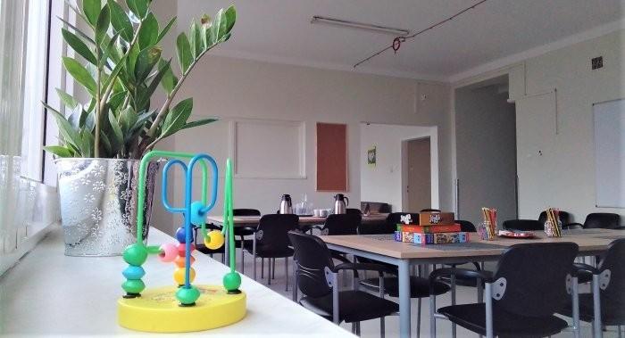 Duża jasna świetlica, stoły i krzesła, parapet z kwiatem, kolorowe gry.